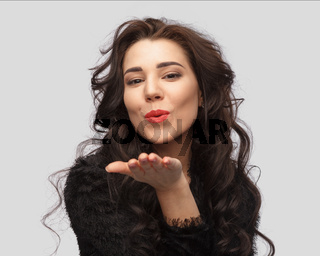 Portrait of a beautiful brunette on a gray background makes a kiss and smiles.