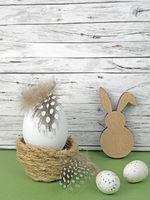 Ostern Hintergrund mit Ostereiern und Osterhase auf grün vor Holz