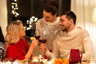 happy friends drinking red wine at christmas party