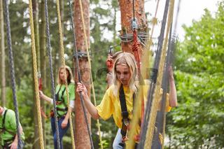 Junge Frau balanciert ängstlich im Hochseilgarten