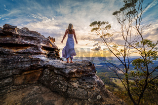 Standing on a rock  with dress blowing in the wind she dreams