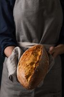 Baker holding fresh homemade bread