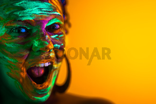 Portrait of girl with fluorescent paint makeup. Dye glowing near UV light. Woman with open mouth in neon light. Night club, party, halloween psychedelic concepts