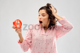 shocked young woman in pajama with alarm clock