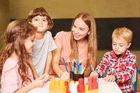 Kinder und Erzieherin haben Spaß im Malkurs
