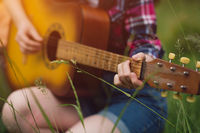 Girl playing guitar out in nature.