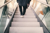 blurred legs of a person go down a staircase
