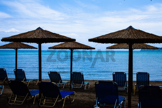 Five Rustic Palapa Umbrellas located at the shoreline of the mediterranean sea with Folding Blue Chairs over the Sand, Beautiful Vacation Landscape at the Beach with sun loungers and parasols