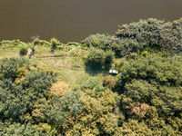 Aerial view from drone recreation place on a bank of river. Top view green trees, meadow and white car. Top view.