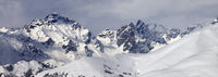Snowy off-piste slope and mountains in clouds