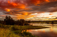 Sunset sky over rural lakes with mountain backdrop
