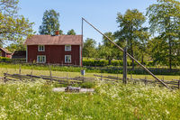 Water well in a meadow with a red cottage