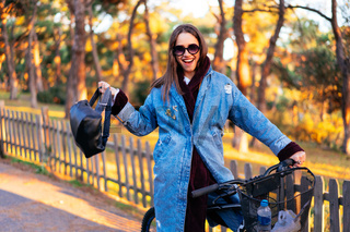 Beautiful young girl on a bicycle posing at the camera