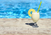 Glass of pinacolada cocktail standing on the swimming pool ledge