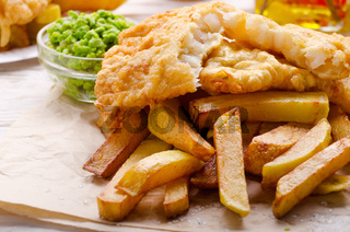 Traditional British street food fish and chips with mushy peas on parchment paper