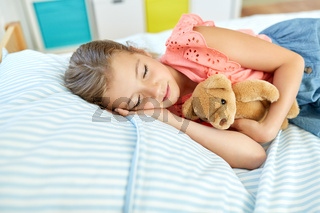 little girl sleeping with teddy bear toy at home