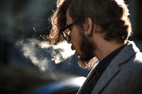 A man with long hair smokes outside
