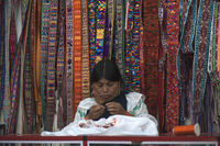 Indian women in national clothes sells the products of her weaving, as usual on weekdays on the most famous markets in South America, in Otavalo, Ecuador