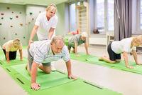 Physiotherapeutin betreut Senioren bei Rückenübung