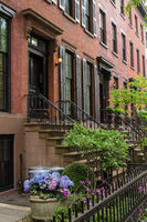 Row of old brownstone buildings along an empty sidewalk block in the Greenwich Village neighborhood of Manhattan, New York City NYC