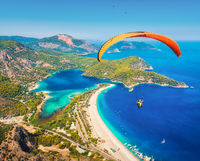 Paraglider tandem flying over sea with blue water and mountains