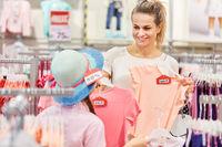 Frau zeigt Mädchen ein Kleidungsstück