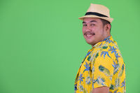 Profile view of happy young overweight Asian tourist man smiling