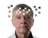 Jigsaw concept of mental illness or dementia with senior caucasian man looking sad into camera