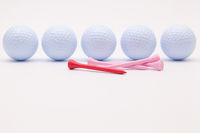 White golf balls and wooden tees on the white background.
