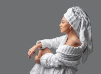 Attractive girl wearing white towel on head and white bath robe, smiling