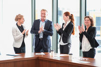 Business group clapping and smiling
