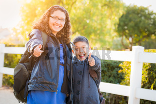 Hispanic Brother and Sister Wearing Backpacks With Thumbs Up