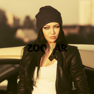 Young fashion woman in leather jacket next to her car