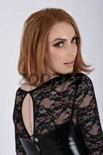 Ashley Foxx, sexy, vollbusige Rothaarige, gekleidet in einem glanzenden schwarzen PVC-Kleid