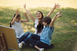 Children and teacher posing with raised hands