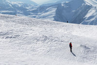 Snowboarder and skiers downhill on snowy slope