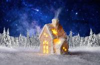 Kleines Haus mit Winterlandschaft und Sternenhimmel