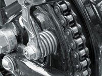 monochrome close up of the drive chain on a black vintage motorbike with chrome fixtures and steel bolts
