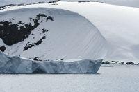 Tabular Iceberg Near The Rocky Coastline Covered With Snow,  Antarctica