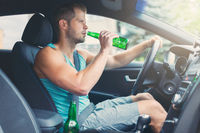 Drunk driver drinking behind the steering wheel of a car