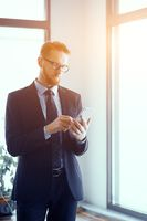 Businessman with smartphone in bright sunny office