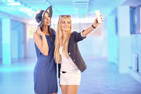 Two pretty young women taking selfie on the phone