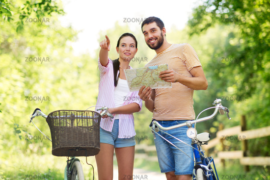 couple with map and bicycles at country in summer