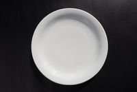 White ceramic round plate on black background
