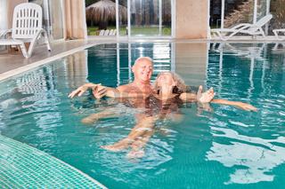 Senior hilft Frau beim schwimmen lernen