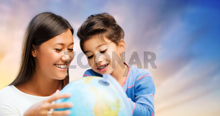 happy mother and daughter with globe over sky