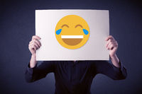 Businessman holding paper with laughing emoticon