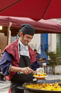 Man smiling, preparing and serving paella (typical spanish meal) in the street of Cartagena in Spain