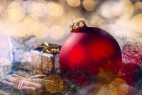 Rote Christbaumkugel mit Weihnachtsdekoration