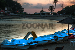 Paddle Boats one with Slide are Stationed along Coastline. Establishments and Trees on the Background. Pinkish Gray Sky Color of Dusk Reflecting on Water.